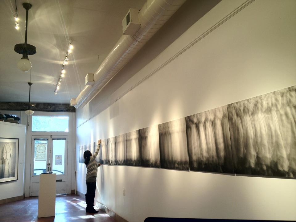 Jung Lee istalling work at NOPA gallery, PhotoNOLA 2011. Photo by Amy Jett