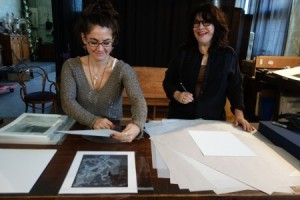 Jenny Bagert assists Josephine Sacbo while signing prints in her studio